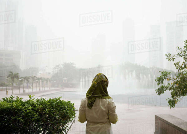 Young muslim woman waiting for rain to end, Kuala Lumpur, Malaysia Royalty-free stock photo