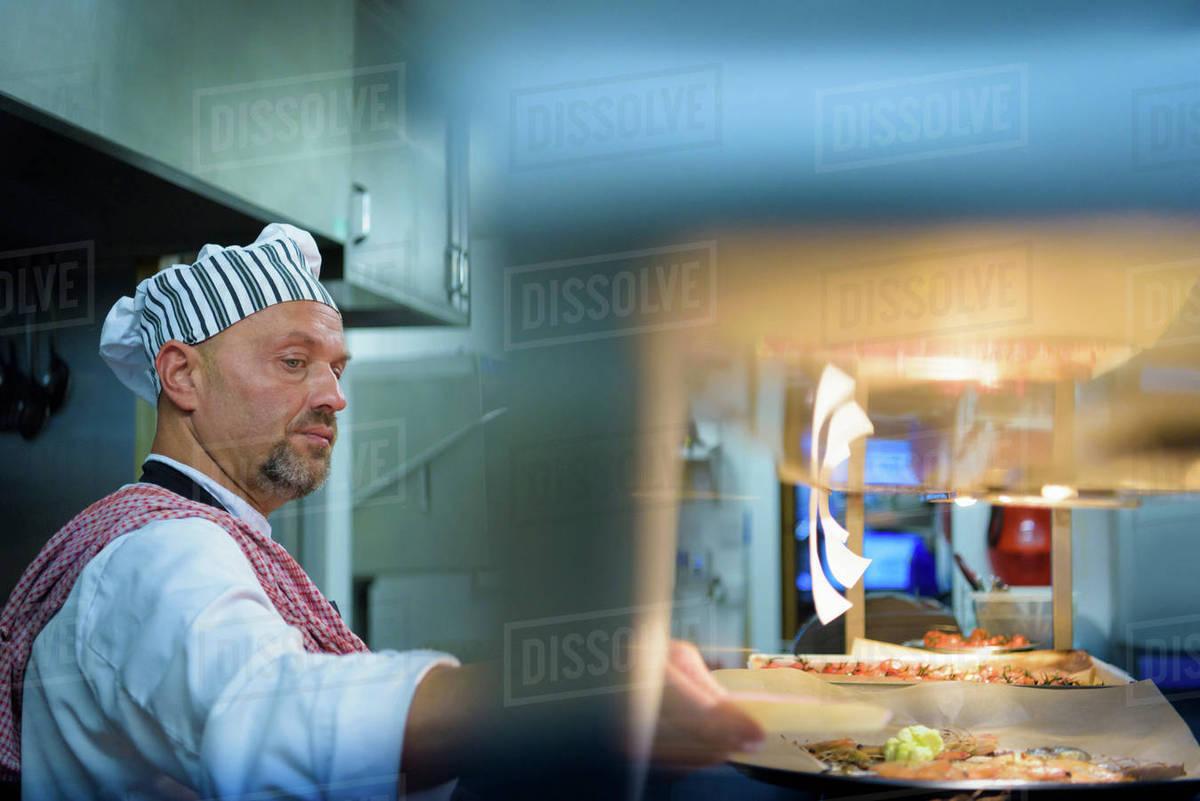 Chef preparing food in traditional Italian restaurant kitchen ...