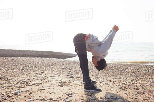 Young man training, bending forward on Brighton beach Royalty-free stock photo