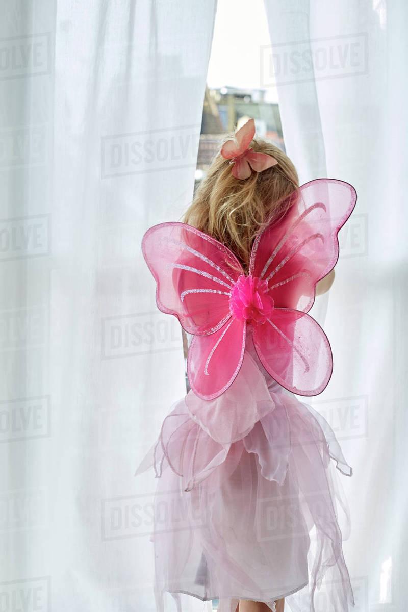 Girl in fairy costume peeking through curtain Royalty-free stock photo