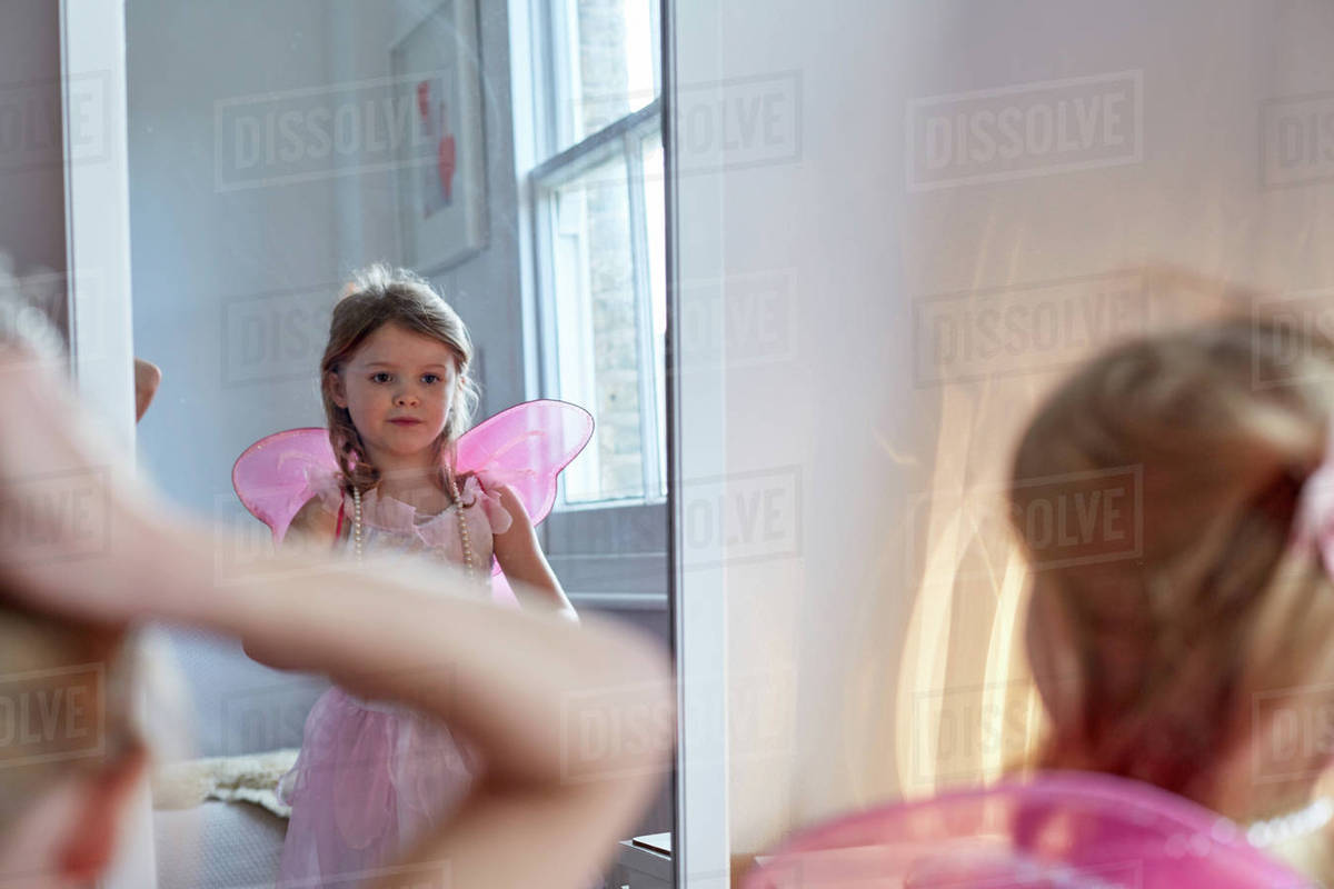 Girl in fairy costume looking into mirror Royalty-free stock photo