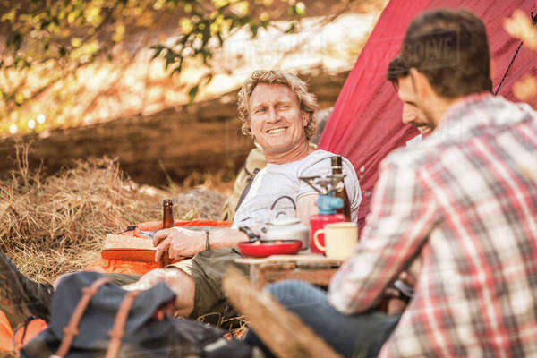 Men camping in forest drinking beer and coffee, Deer Park, Cape Town, South Africa Royalty-free stock photo