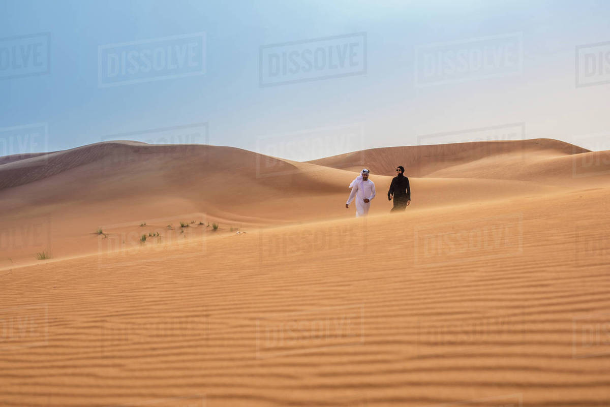 Distant view of couple wearing traditional middle eastern clothes walking  on desert dune, Dubai, United Arab Emirates stock photo