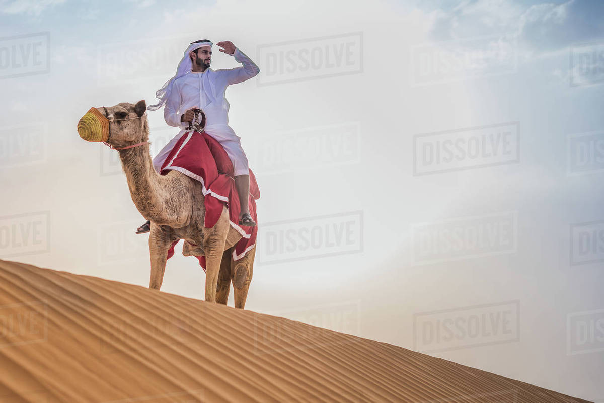 Man wearing traditional middle eastern clothes riding camel in man wearing traditional middle eastern clothes riding camel in desert dubai united arab emirates thecheapjerseys Choice Image
