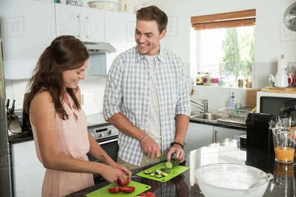 Couple cutting vegetables in kitchen Royalty-free stock photo