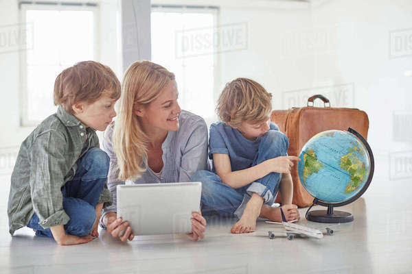 Mature woman and two son's sitting on floor looking at globe Royalty-free stock photo