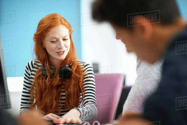 Young male and female college students at computer desk teamworking Royalty-free stock photo