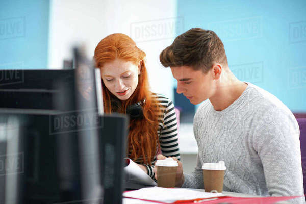 Young female and male college students reading at computer desk Royalty-free stock photo
