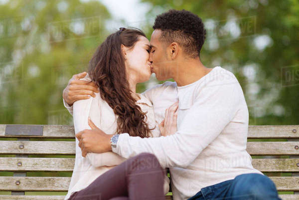 Young couple on park bench kissing Royalty-free stock photo
