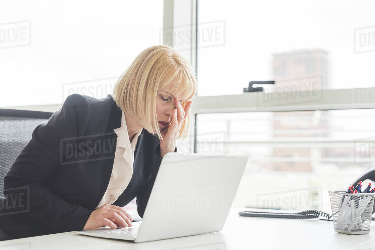 Stressed mature businesswoman working on laptop at office desk