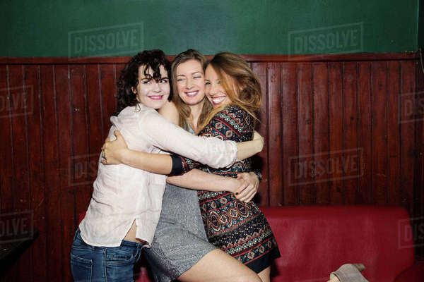 Three adult female friends having group hug in bar Royalty-free stock photo