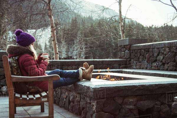 Young woman sitting on bench with fire pit, Girdwood, Anchorage, Alaska Royalty-free stock photo