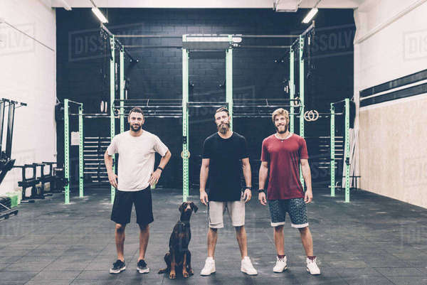 Portrait of three male cross trainers and dog in gym Royalty-free stock photo