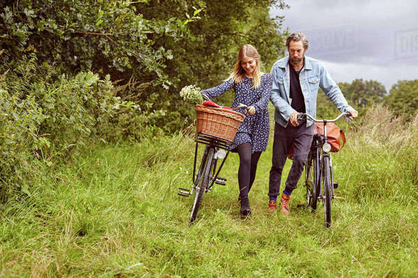 Couple pushing cycles along rural path Royalty-free stock photo