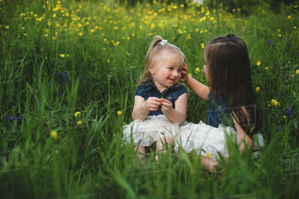Girls sitting in wildflower meadow face to face smiling Royalty-free stock photo