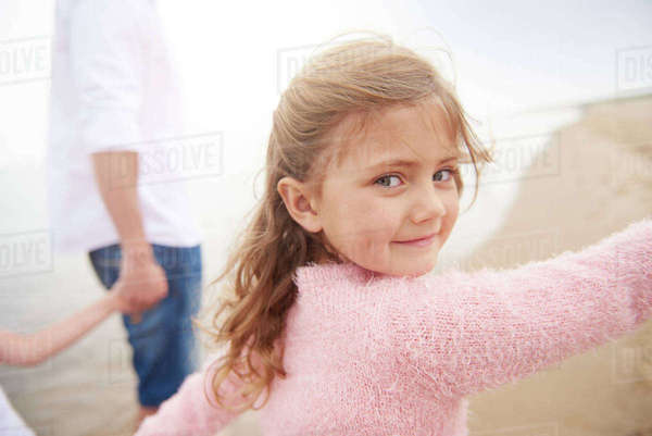 Family walking on beach, daughter looking over shoulders Royalty-free stock photo