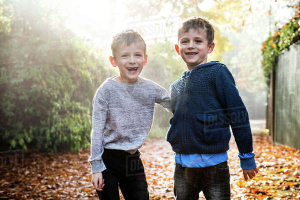 Portrait of twin boys, outdoors, surrounded by autumn leaves, laughing Royalty-free stock photo