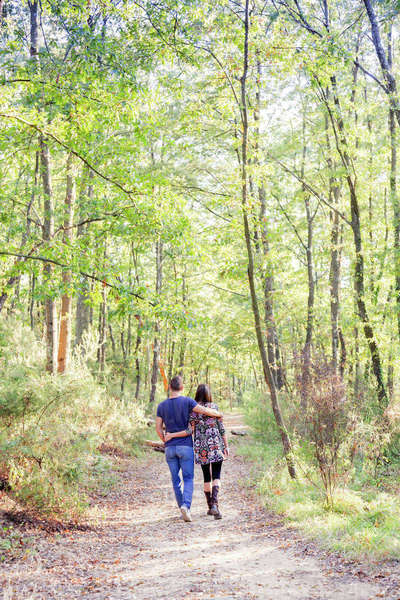 Rear view of couple walking on tree lined path Royalty-free stock photo