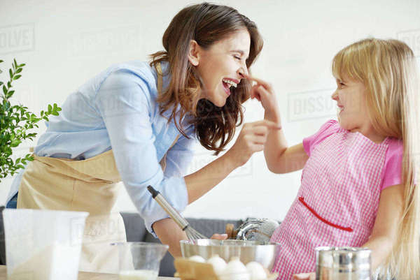Mother and daughter baking together, fooling around Royalty-free stock photo