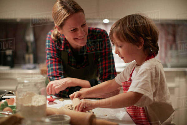 Mature woman and son rolling dough on kitchen counter Royalty-free stock photo