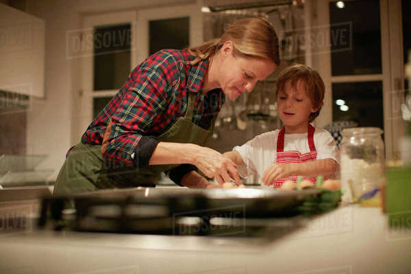 Mature woman helping son with baking on kitchen counter Royalty-free stock photo