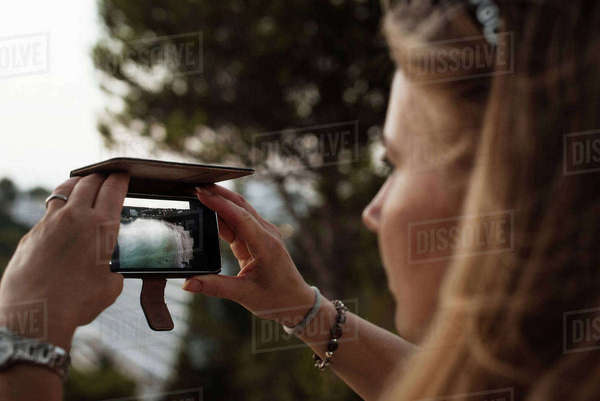 Woman taking photograph with smartphone, Menorca, Spain Royalty-free stock photo