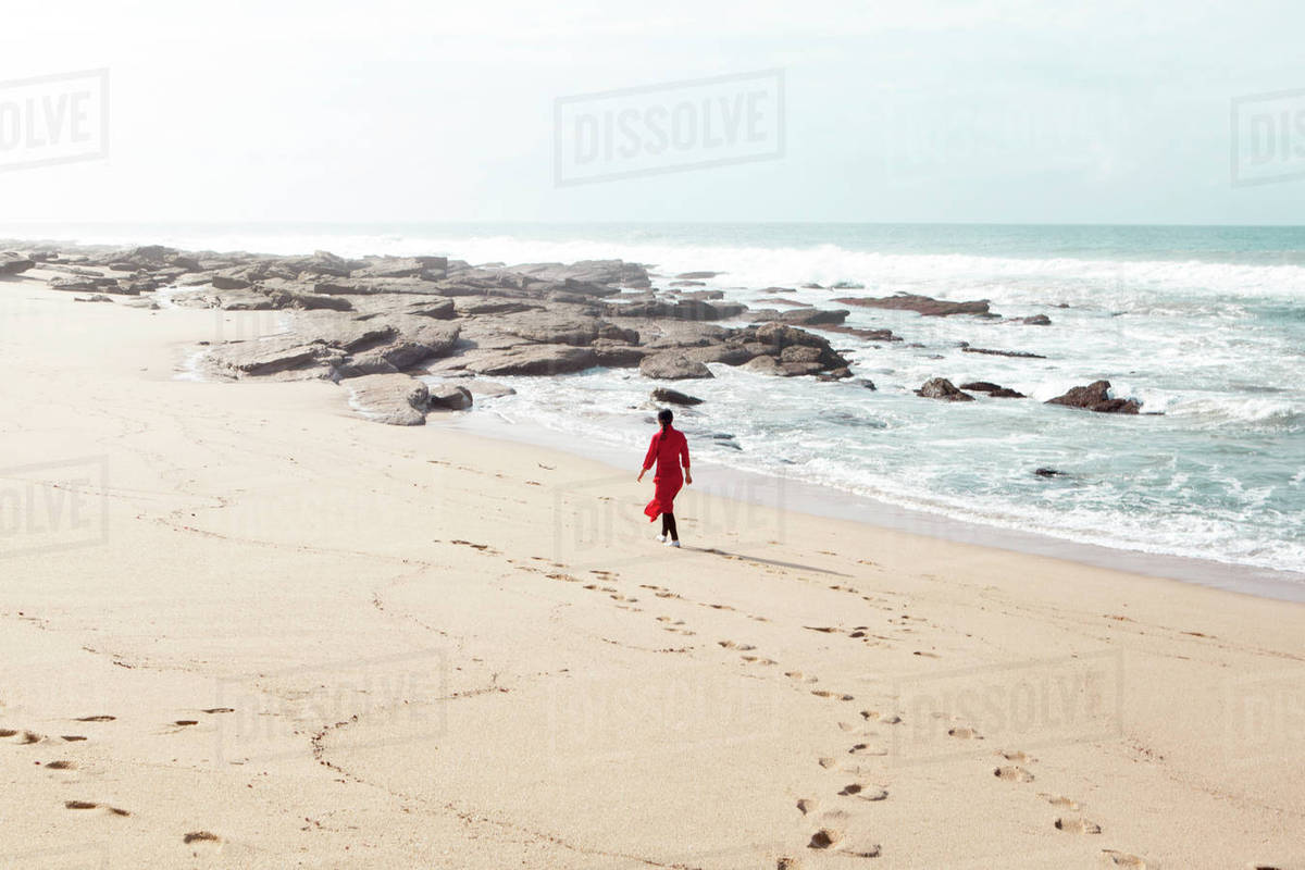 Woman Wearing Red Dress Walking Along Beach South Africa