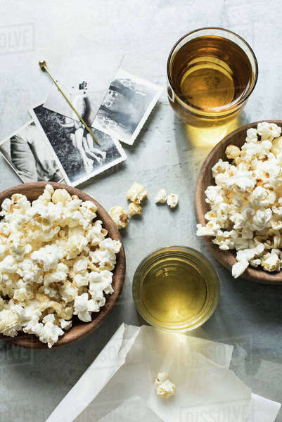 Still life of popcorn and drink, beside old black and white photographs, overhead view Royalty-free stock photo