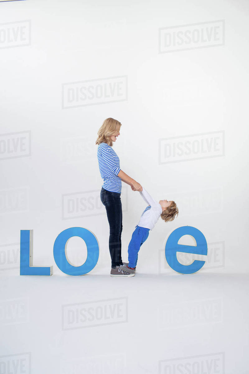 Mother and son holding hands, standing between three-dimensional letters,  creating the word LOVE stock photo
