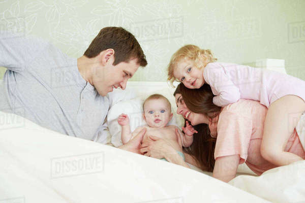 Female toddler and baby sister playing in bed with parents Royalty-free stock photo