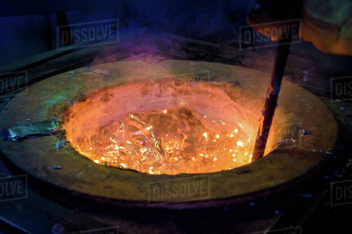 Worker stirring molten aluminum alloy in precision casting factory, close  up stock photo