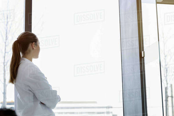 Female doctor looking out of window, rear view Royalty-free stock photo