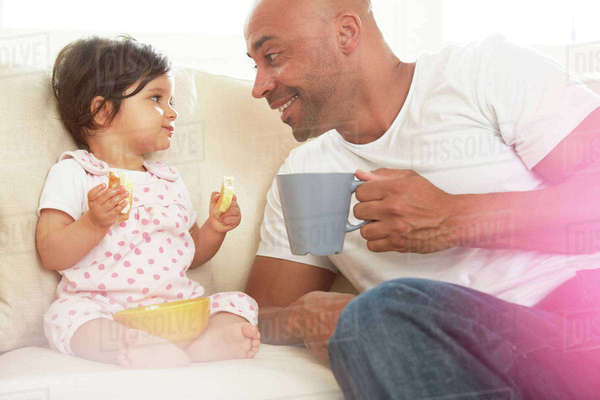 Baby girl and father sitting on sofa eating snack Royalty-free stock photo