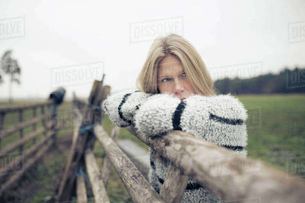 Young woman leaning forward on wooden fence Royalty-free stock photo
