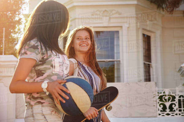 Teenage girls with ball and skateboard in street, Cape Town, South Africa Royalty-free stock photo