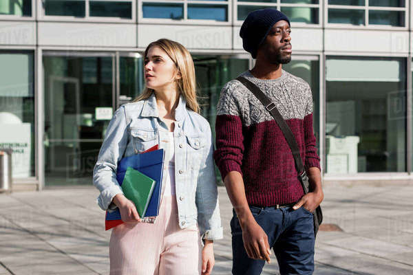 Young man and woman walking outdoors, woman carrying notebooks and files Royalty-free stock photo