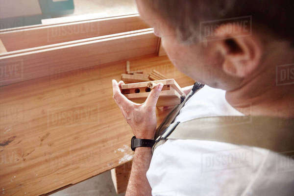 Over shoulder view of carpenter inserting wooden dowel at workbench Royalty-free stock photo