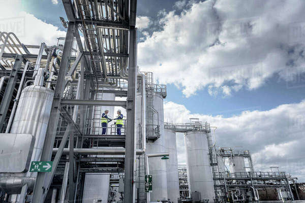 Workers on top of process plant in oil blending factory, low angle view Royalty-free stock photo