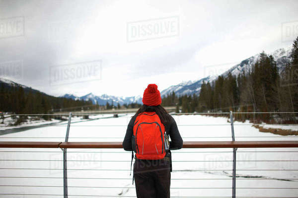 Hiker on bridge looking at snow capped mountains, Banff, Canada Royalty-free stock photo