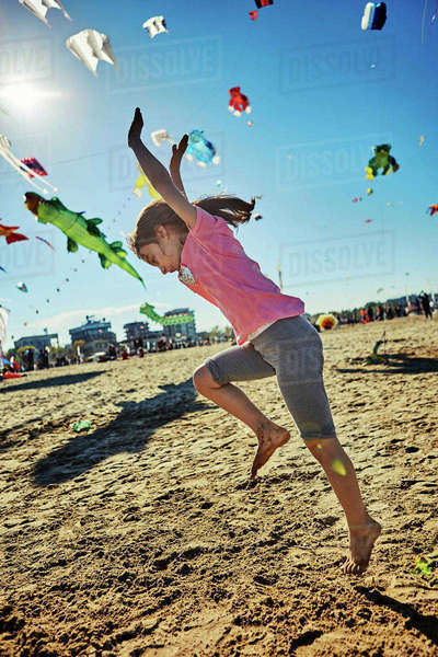 Young girl doing cartwheel on beach, kites flying in sky behind her, Rimini, italy Royalty-free stock photo