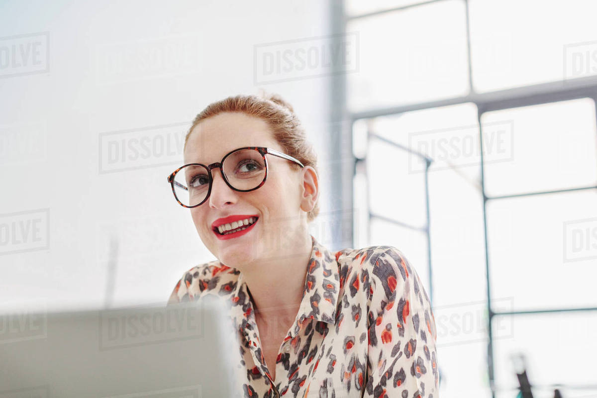 woman in office wearing reading glasses looking away smiling stock
