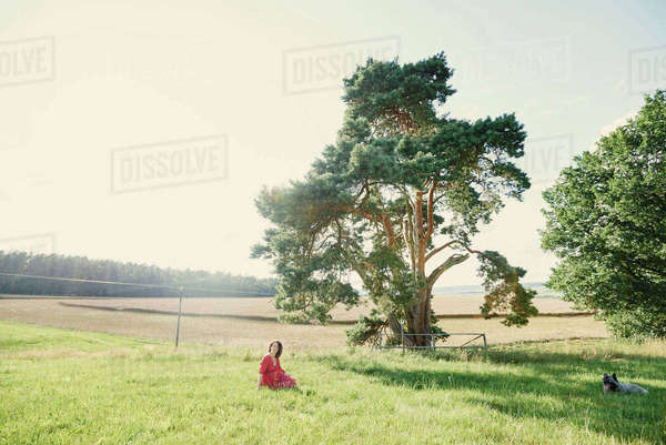 Distant view of pregnant woman sitting in field landscape Royalty-free stock photo