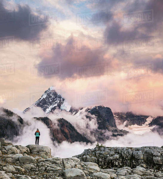 Hiker looking at clouds on snow covered mountains, Mount Baker, Washington, USA Royalty-free stock photo
