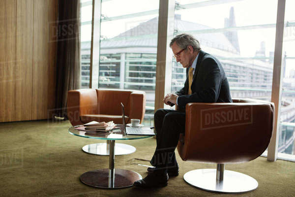 Businessman using laptop in coffee area in office, London, UK Royalty-free stock photo