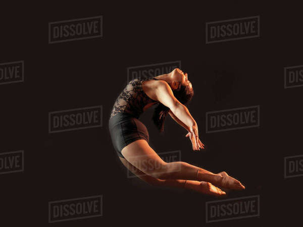 Low key shot of young female dancer bending backwards whilst leaping mid air Royalty-free stock photo