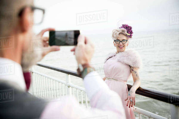 Over shoulder view of man taking photograph of 1950's vintage style mature woman on pier Royalty-free stock photo
