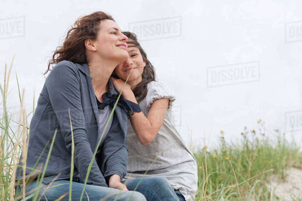 Mother and daughter sitting on beach Royalty-free stock photo