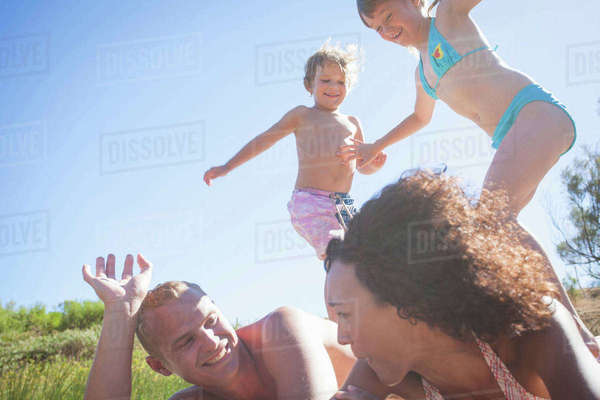 Man and woman lying on their fronts with children standing on their backs Royalty-free stock photo