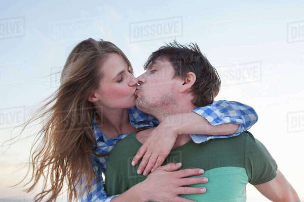 Couple kissing, woman with arms around man Royalty-free stock photo