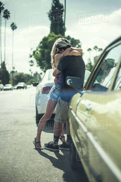 Young couple leaning against car, arms around each other Royalty-free stock photo